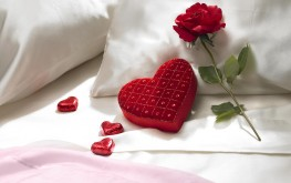 Valentine's Day romantic red rose and heart shaped candy box with red heart shaped chocolate candy on pillow of bed.